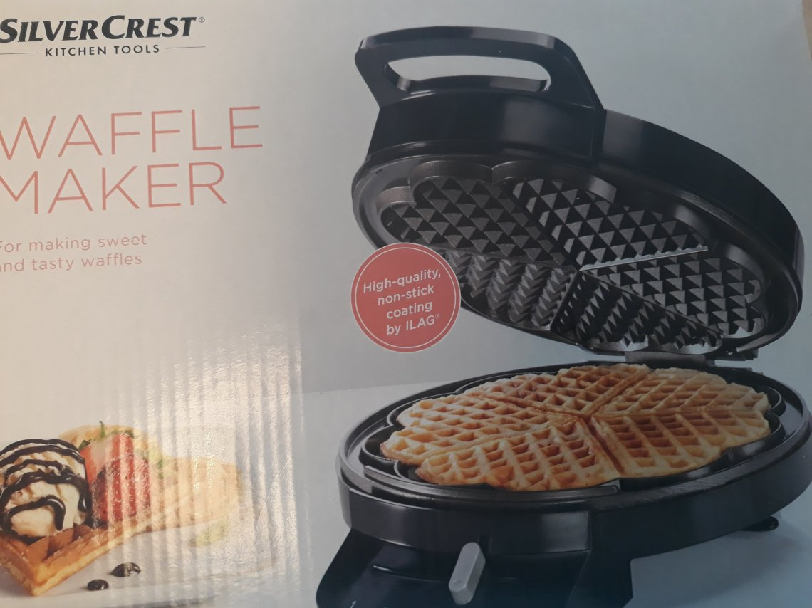 Picture of the box the waffle maker came in. It's a white box with a picture of a cooked waffle in the machine on it